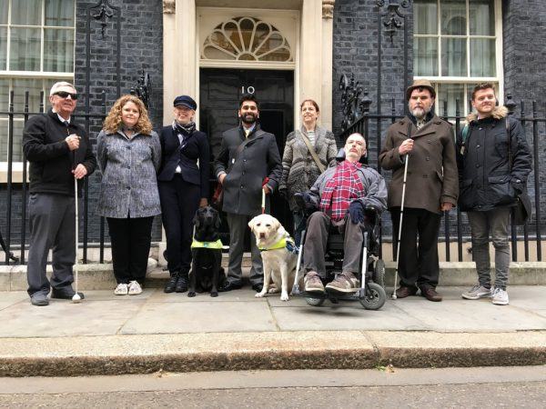 There're are 8 people and two guide dogs in the photograph which was taken outside Number 10. These included - Michelle Hough, the Chair of Transport for All, Alan Benson, who is in his wheelchair and two of his colleagues, the President of the NFBUK, Andrew Hodgson and Sandy Taylor, from NFBUK Scotland, both of whom are holding white canes, along with student Charlotte Nickson, with her Guide Dog Layla and Dr Amit Patel with his Guide Dog Kika.
